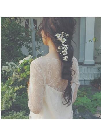 後ろに一つに束ねたヘアスタイルは、落ち着いた大人にぴったり。白い花だけを髪に挿して、憧れのナチュラルウェディングスタイルの完成です。