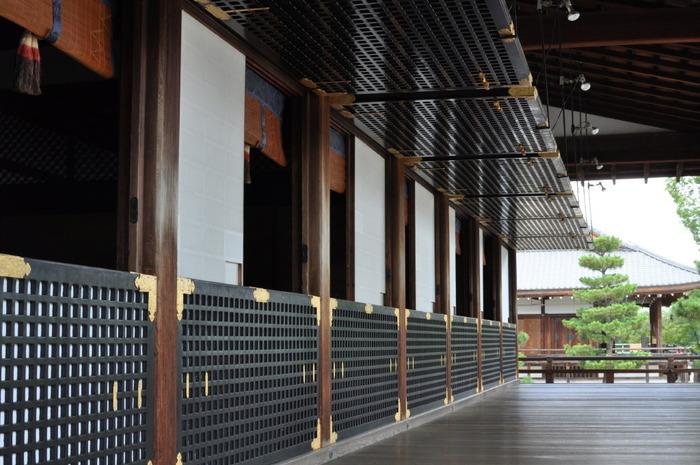 金の留め具が施された黒色の格子は「蔀戸(しとみど)」。 *蔀戸は、長押から吊り下げた建具のことで、通常上下に分かれ、寝殿造の建物や神社の拝殿等で外回りに用いられています。【画像は、宸殿の南面の蔀戸】