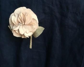 冬に咲く鮮やかなサザンカの花で染めた布のコサージュ。淡いピンクがかったベージュで、大人の優しい雰囲気があります。