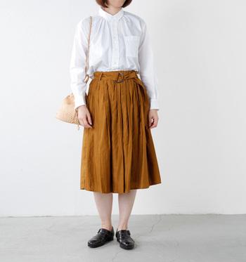 コットンの白シャツとマスタードカラーのプリーツスカートを合わせたスタイリング。ウエストインできちんと感のある大人フェミニンな着こなしです。