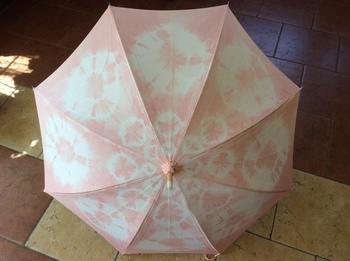 桜染めも、人気の高い草木染めですね。写真は、桜の枝で染め液を作り、手染めした綿地の日傘。絞りの模様も愛らしい♪