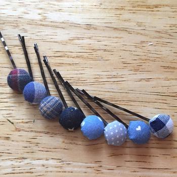 くるみボタンを使ったヘアピン。くるみボタンの足を取り、ヘアピン金具をボンドで貼って作ります。貼り付け用のヘアピンを使わなくても、ボタンの足にヘアピンを通すだけでもOKです。