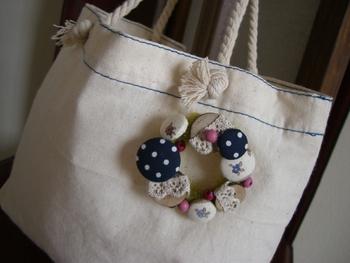 くるみボタンをいっぱい使ってリース型にしたブローチ。シンプルなバッグの雰囲気がガラリと変わりますね。