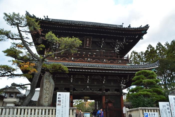 """「清涼寺」は、境内に本堂や多宝塔等が建ち並ぶ広大な寺院。 本堂に安置されている釈迦如来立像から、地元では""""嵯峨の釈迦堂さん""""と親しまれています。 【画像は、京都府指定文化財の「仁王門」。嵯峨野のちょうど真ん中に位置するため""""嵯峨の顔""""とも称されています。】"""