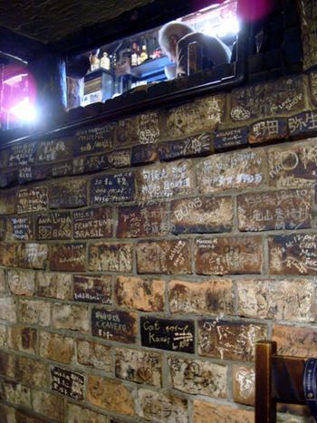 外観だけでなく、店内の雰囲気も個性的。レンガ造りの壁には、過去にお店に来た人々のコメントがびっしりと書かれています。