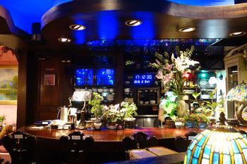 場所を変えると、ブルーの照明が印象的な大人の空間に。レトロなステンドグラスのランプも多数並び、独特の雰囲気が漂っています。