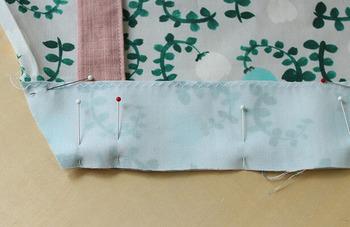 エプロンと襟、首紐をマチ針で留めて、少し縫い代が出るくらいにミシンで縫っていきます。襟の重っていない部分は、事前にジグザグ縫いしておくとキレイに仕上がります。