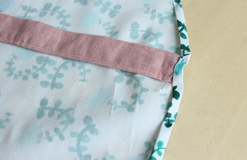 腰紐は三つ折りにした布の下にマチ針で留めて、ミシンで縫いましょう!腰紐は本体布の腰部分に、まっすぐ縫い付けていきます。