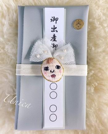 レザーで包むご祝儀袋は、水引に手刺繍でひと針ひと針丁寧に仕上げた赤ちゃんの顔。赤らんだ頬とぱっちりとした目が可愛らしい♪