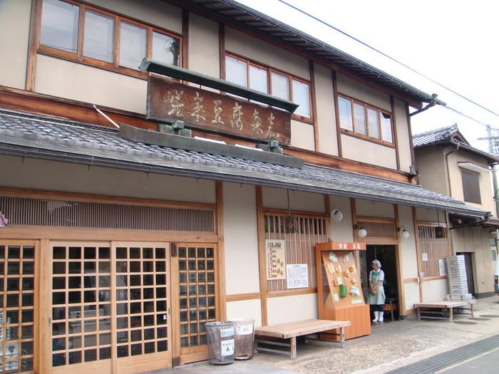 """嵯峨野の老舗豆腐店「森嘉」。 京都の有名料理店や寺院が贔屓にする、京都屈指の有名店です。清涼寺の仁王門の並びに工場兼店舗があります。 創業は、江戸期・安政の頃。 厳選した材料と、創業当時から湧き続ける地下水で作る豆腐は、""""やわらかく、腰が強く、なめらか""""。現在でも、豆腐や油揚げ等など全ての商品は、一つ一つ丁寧に手作業で作り続けています。"""