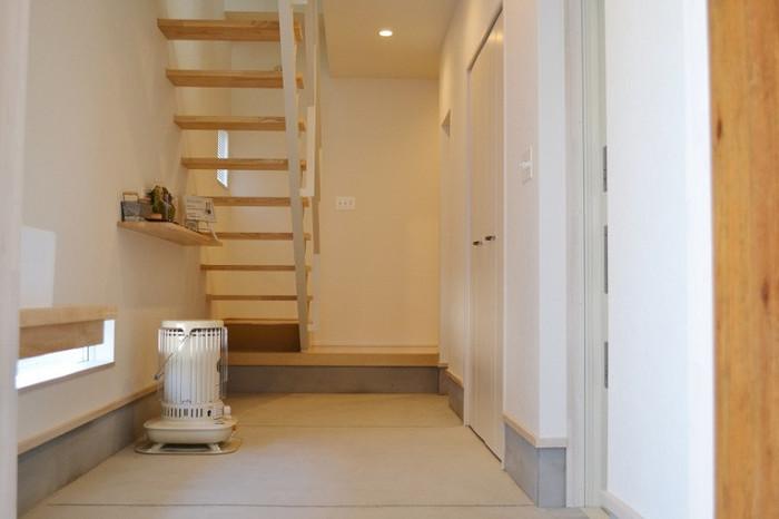 こちらの広々とした土間は、飾り棚の上だけにモノを集めて、そのほかの部分をすっきりとさせています。モノがないと壁や床の白さが際立ちます。