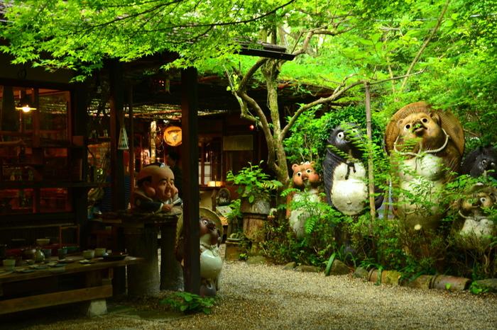 """「小陶苑(ことうえん)」は、祇王寺から二尊院へ向かう街道沿いにある""""信楽焼き""""の専門店。 モミジに覆われた店には、狸の置物や花瓶、食器や壺等など信楽焼きが所狭しと並んでいます。眺めるだけでも楽しいお店です。「小陶苑」の中庭には広い茶席が設けられ、愛らしい陶器を眺めながら、美味しい抹茶や季節の和菓子が頂けます。"""