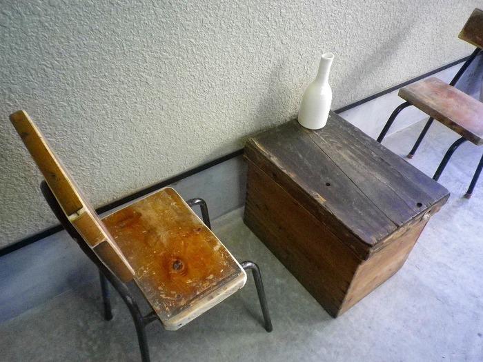 こちらアイアンと古材の椅子に合わせたアンティークな茶箱。  コンクリートの床に直に置かれて味わいが増します。