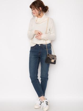 フェミニンなゆる~り開いたタートルネックのカシミヤニットセーターも◎ スポーティーな靴とジーンズでボーイッシュに。小さなショルダーバッグで甘辛ミックスコーデのできあがり。