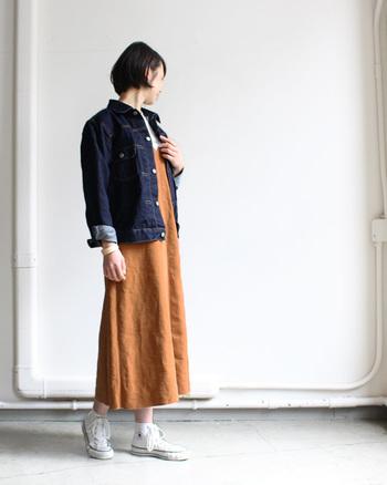 ロングワンピースに今年トレンドのオーバーサイズのデニムジャケットを羽織ったスタイル。袖をロールアップしたこなれ感のある着こなしです。