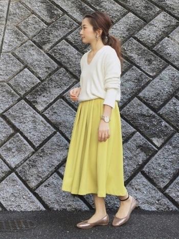 鮮やかなイエローのスカートにも負けない足元の存在感。歩く姿をエレガントに彩ります。