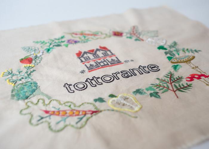 こちらはご友人、料理家の黄川田としえさんのために作られた 作品。丁寧に刺繍された苺や菜の花、相手を思って作られた品 からは愛情を感じますよね。