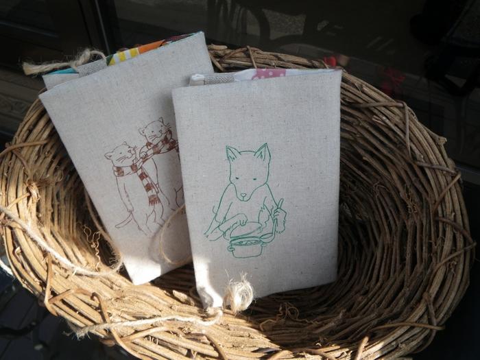 手作りのブックカバーなどを販売するお店「旅するミシン店」。他にもバッグやポーチ、便せんなどもあります。描かれたイラストは全て、店主であるイラストレーターうえきななせさんの作品です。