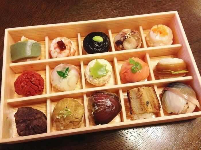 ●花梓侘(かしわい)の「つまみ寿司」  花梓侘は、京都北山で人気の創作料理店。生麩や穴子、しめ鯖や若竹等など、多種多彩な具をのせた、手毬寿司の詰め合わせ弁当です。見た目通りに、味わいもはんなりとして艶やか。10貫入り、15貫入りがあります。(SUVAKOでも、6貫入が販売されています。)