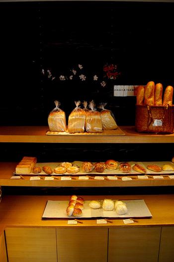 ダークな配色の内装が印象的な店内。ズラリと並べられた可愛らしいパンたちがシンプルでシックな背景により引き立っていますね。