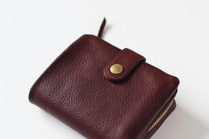 こちらは2つ折り財布。バッグに入れてもじゃまになることもなく使いやすい、ほどよいサイズ感。ゴールドのボタンとチャックがいいアクセントになっています。