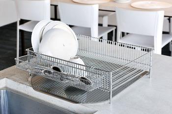 シンプルでスタイリッシュな有元葉子さんの水切りカゴ、ラパーゼ。お皿から落ちた水は、水受けからシンクへと流れていく設計。