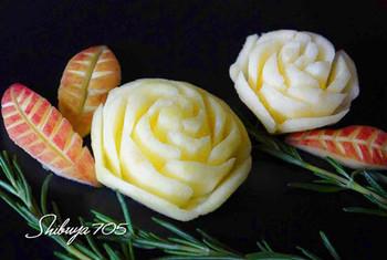 りんごでバラの花を作りましょう。下から中央部分をずらさないよう、らせん状に切込みを入れてつくります。よく切れるナイフを使って。