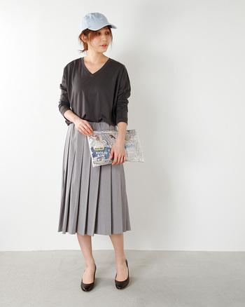 Leeのデニム調のキャップをプリーツスカートに合わせたミックスコーディネート。カジュアルなクラッチバッグも合わせて、遊び心のあるスタイルに。