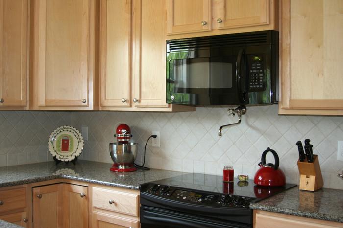 真っ白のタイルを斜めにレイアウトしたかわいらしいキッチンです☆ 赤のポイントも、とっても素敵ですね♪