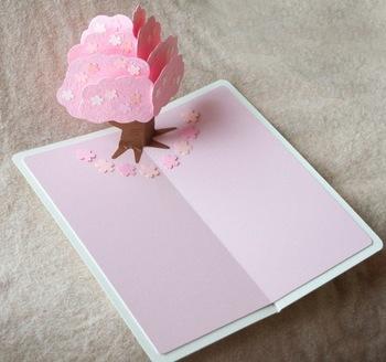 """こちらのポップアップは、本の台紙になる紙と、桜の木になる紙の2枚の紙をベースにして作ったもの。 基本この形での作り方は、台紙になる紙は""""谷折り""""、飾りつけの紙は""""山折り""""になっています。"""