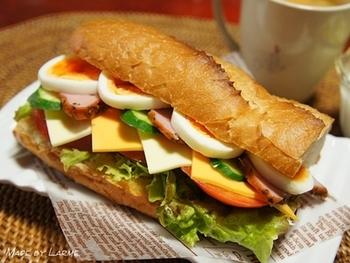 フランスパンの厚みを半分に開いて、そこに卵やベーコン、チーズとたっぷりの野菜を挟んだ見た目がとても美味しそうなサンドイッチ。フランスパンを少し押さえて食べると、具材の水分がうまい具合に吸ってくれて食べやすくなります。