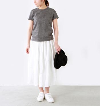 オーガニックコットンのコンパクトなTシャツに白のフレアスカートを合わせたコーディネート。ブラックのハットを合わせて、コーディネートを引き締めて。