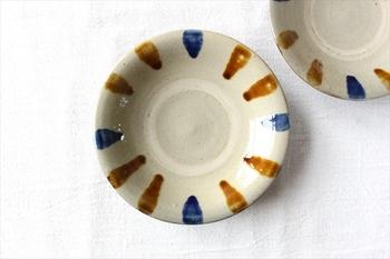 手描きの点打ちが温かみのあるお皿。中央には白くて丸い線が入っていますが、これは「蛇の目」というもの。器を重ねて焼くときに、上の器と下の器がくっついてしまわないように、釉薬をはがすためにできる模様です。この蛇の目もやちむんの特徴の一つ。