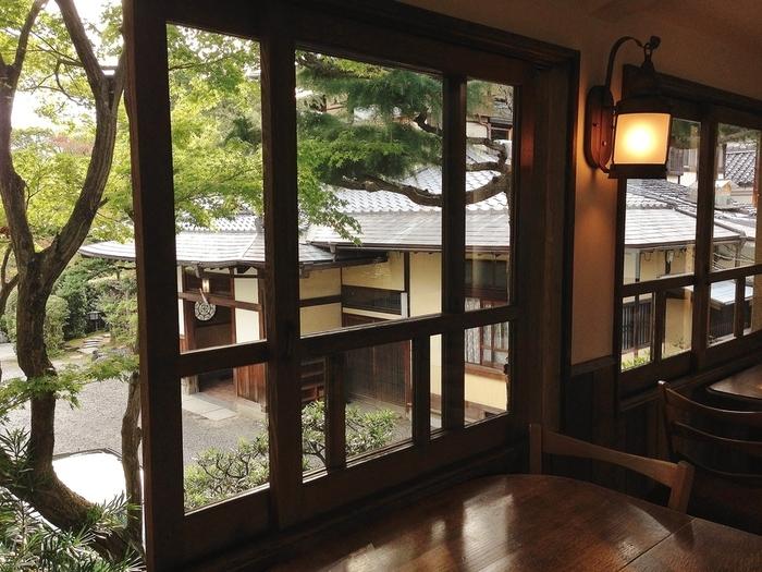 「真如堂」から徒歩で5,6分に位置する「吉田山荘」は、昭和天皇の義弟・元東伏見宮家別邸を改装した料理旅館。緑豊かな敷地には、宿泊者以外でも気軽に立ち寄れるカフェがあります。【画像は「カフェ真古館」内からの眺める本館入口。】