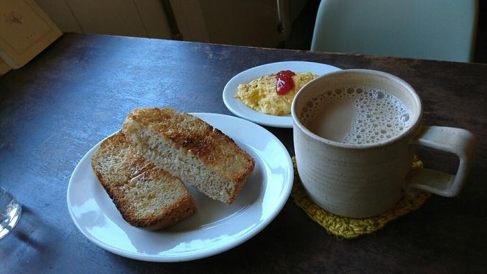 長野県産の石臼挽き小麦粉を用いた「SWISS coffee and plants 」の自家製パンと焼き菓子は、風味豊かで美味しいと人気です。 【画像は、『モーニングサービス』の自家製パンのバタートースト・ミニオムレツ・ミルクコーヒー。朝9時から営業のこの店では、11時まで美味しいモーニングが頂けます。】