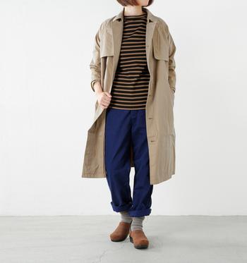 ベージュのトレンチコートのインナーにブラウン系のバスクシャツを合わせて。サボも同系色で統一した秋らしいパンツスタイル。