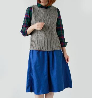 ざっくり模様編みのニットベストにチェック柄のシャツとブルーのスカートを合わせたスタイリング。