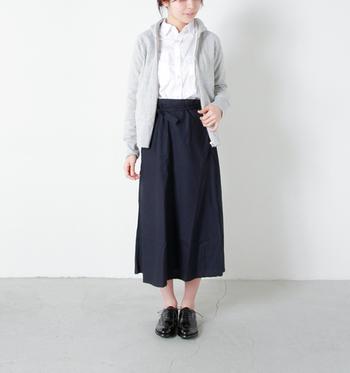 ホワイトTシャツとネイビースカートのとてもシンプルな着こなし。足下を黒の革靴で引き締めて洗練された印象に。