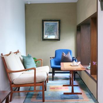 """奥まったソファ席も素敵です。  ブルーのイージーチェアは『フィン・ユール』の「NV-53」。左側の2人掛けソファは、""""デンマーク家具デザインの父""""と呼ばれた『オーレ・ヴァンシャー』デザインのものだそう。"""