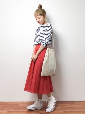 鮮やかなオレンジ色のスカートを合わせて。小物は白で統一して爽やかにまとめるのがポイントです。