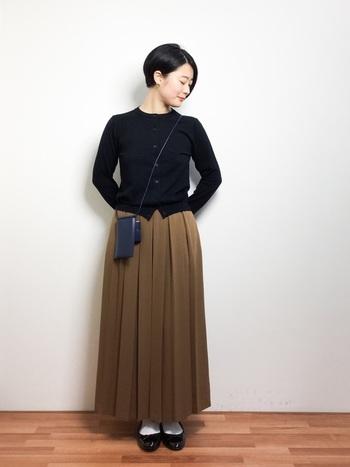 クラシカルなトップスとプリーツスカートの組み合わせ。エナメルのバレエシューズが落ち着いたスタイリングのアクセントに。
