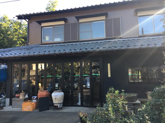 三芳町のさつまいも農家が集まる地域の一角にあるのが、さつまいも農家の古民家を改装してオープンしたさつまいも料理のお店、その名も「オイモカフェ」です。 モダンな印象の黒の外観と、店先にオブジェのように置かれている美味しい焼き芋を作るための「壺」の組み合わせが、さり気なくオシャレでもあります。