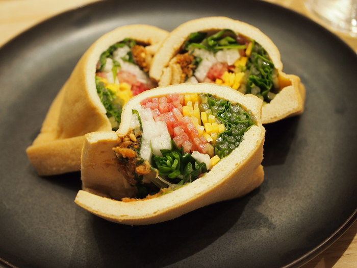 """一品料理も創意工夫に満ちています。国産のやまとはちみつ入りの甘辛だれをじっくり含ませたお揚げの中に、季節の野菜が入った""""野菜成り(やさいなり)""""も彩り豊かで美味しそうですね。"""