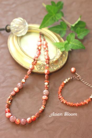 オレンジ系の石を繋げたキュートなネックレスとブレスレット。ビタミンカラーが元気を運んできてくれそう!