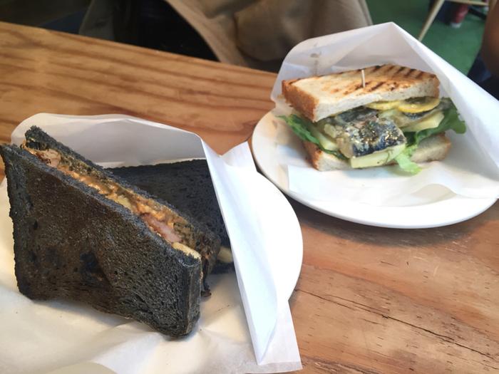 竹炭入り天然酵母イギリスパンに、自家製ベーコンやバナナを挟んだホットサンド(手前)と、鯖のマリネのサンドイッチ(奥)。どちらも他にはないしっかりとした味なので、つい通いたくなります。