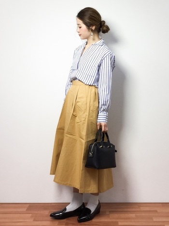 ピンストライプのきれいめシャツにフレアスカートを合わせた大人なレディスタイル。足元をヒールではなく白靴下を合わせたローファーにすることで、ワンランク上のおしゃれな着こなしに。