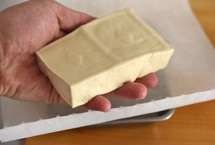 絹ごし豆腐でももちろんOKですが木綿豆腐の固さの方が作りやすく、歯ごたえもあるようです。 豆腐チップスをうまく仕上げるポイントは、しっかり水切りすること! ざるに豆腐を乗せて冷蔵庫で半日くらい水切りをするか、時間がない方は、豆腐をキッチンペーパーにくるんでお皿に乗せ、電子レンジで3~4分ほどチンすればOK!