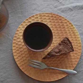 桜の木で作られた削り出しのはちのすが印象的な丸型の木のお皿は、凛としていて気が引き締まります。ダークなチョコレートケーキと陶器を乗せて、ゆっくりティータイムを楽しみたいですね。