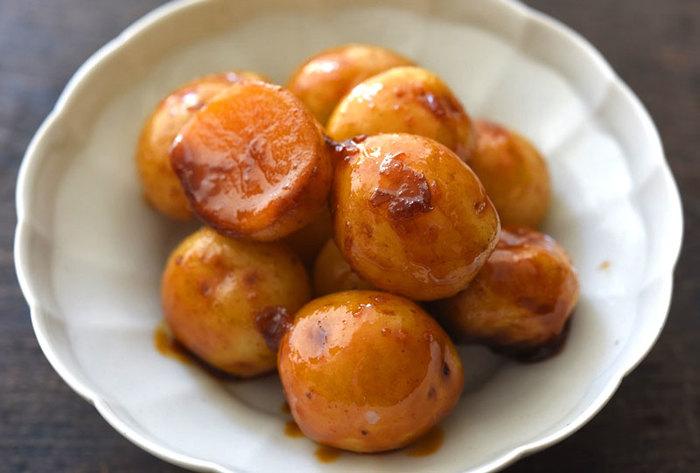 小粒の新じゃがが手に入ったら、ぜひ作ってみたい煮物です。油で炒めず、こっくりと煮込んだあめ色の新じゃがは、お惣菜やお弁当のおかずとして重宝します。表面が甘辛く、中はおいもの味をしっかり感じられます。