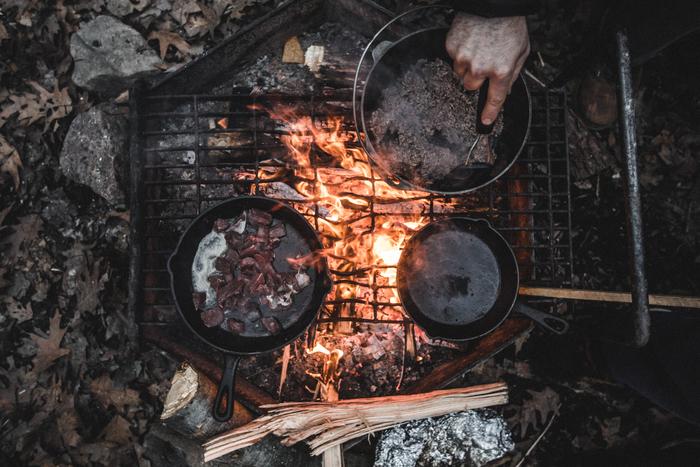 そんな時、ダッチオーブンやスキレットやアルミ鍋、ホーローカップなど、幾つか小回りの効く道具を用意しておくと便利です。特に、最近人気のダッチオーブンがあれば、炒めものや煮もの、蒸しもの、豪快なお肉のロースト、さらにはパンだって焼けちゃいます。頑丈で厚みのある蓋の上にも焼いた炭を載せて加熱します。